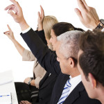 Business lecture with hands raised in the air